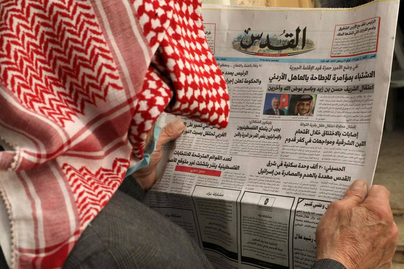 """An elderly Palestinian man reads the daily newspaper Al-Quds, bearing on its front page headlines about the latest events in neighbouring Jordan, in the occupied-West Bank town of Hebron, on April 4, 2021.  Jordan's official media warned today that security and stability are a """"red line"""", a day after several senior figures were detained and a half-brother of King Abdullah II said he was put under house arrest. / AFP / HAZEM BADER"""
