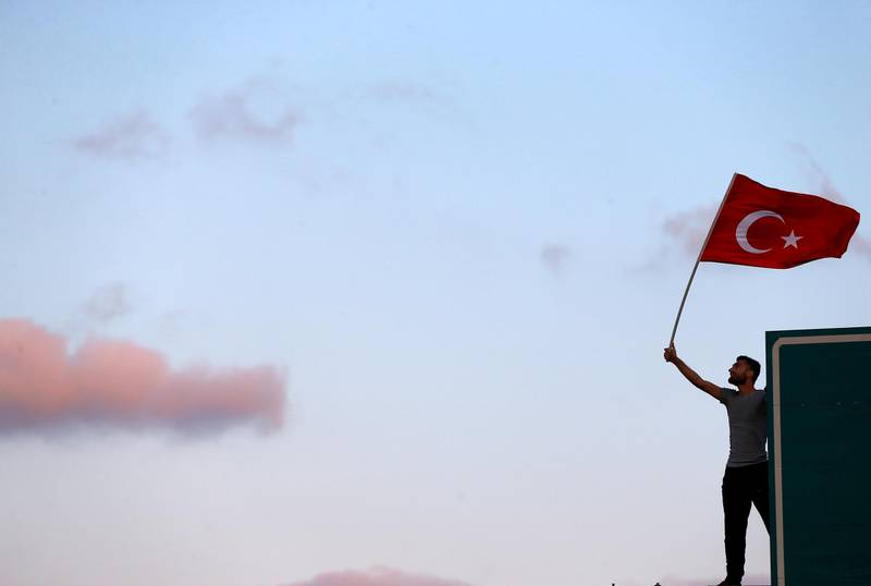 FILE PHOTO: A man waves a Turkey's national flag as he attends a ceremony marking the first anniversary of the attempted coup at the Bosphorus Bridge in Istanbul, Turkey July 15, 2017. REUTERS/Osman Orsal/File Photo