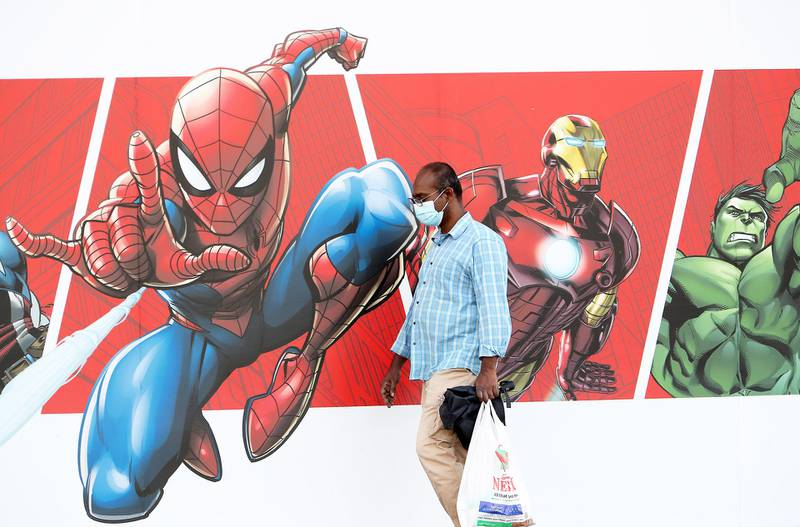DUBAI, UNITED ARAB EMIRATES , December 25 – 2020 :- One of the person wearing face mask and passing by the superheros poster in Deira Dubai. ( Pawan Singh / The National ) For Standalone/Online/Instagram