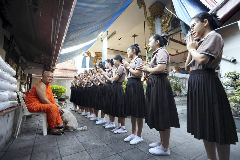 Bangkok-Thailand-The Monk with Gamo the beloved dog of the school. The Students Line up for pay respect to the abbot of the faculty 6Th, (As their are many faculties in the Temple of Dawn),  Faculty 6th is the only faculty that have run the Learning Center).  Sasamon Rattanalangkarn for The National