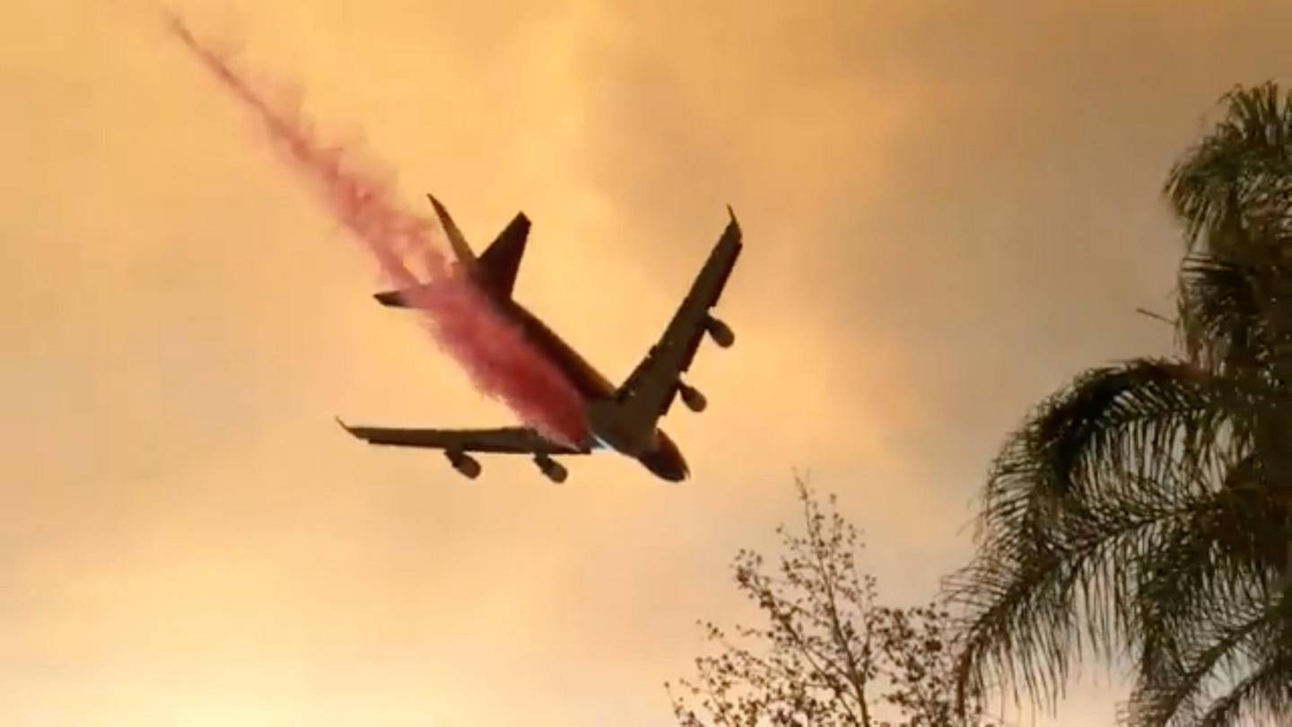 A plane dumps fire retardant over the Holy Fire as it spreads in Lake Elsinore, California, the U.S. August 8, 2018 in this still image taken from a video obtained from social media. Lake Elsinore City Hall/via REUTERS THIS IMAGE HAS BEEN SUPPLIED BY A THIRD PARTY. MANDATORY CREDIT. NO RESALES. NO ARCHIVES.