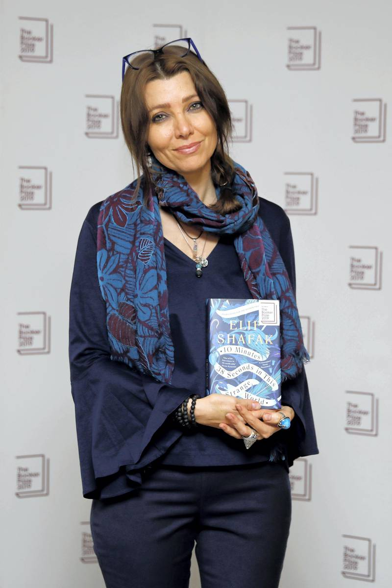 Turkish-British author Elif Shafak poses with her book '10 Minutes 38 Seconds in This Strange World' during the photo call for the authors shortlisted for the 2019 Booker Prize for Fiction at Southbank Centre in London on October 13, 2019. (Photo by Tolga AKMEN / AFP)