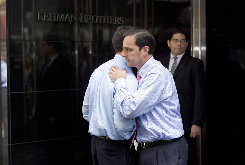 """(FILES) In this file photo taken on September 15, 2008 two men hug outside of Lehman Brothers headquarters in New York. - It was """"Lehman Weekend."""" The moment in September 2008 when the 150-year-old investment bank Lehman Brothers collapsed, precipitating the worst global economic crisis since the 1930s. Monday, September 15, 2008, at 1:45 am, Lehman Brothers filed for bankruptcy, taking the world by surprise leaving well over $600 billion in debt, as well as 25,000 employees in shock. (Photo by NICHOLAS ROBERTS / AFP FILES / AFP)"""