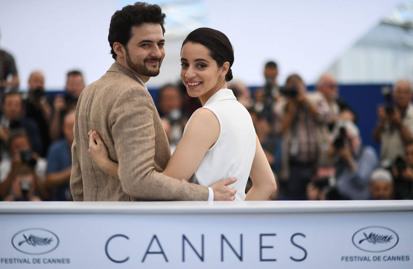 """TOPSHOT - Egyptian director A.B Shawky (L) and producer Dina Emam pose on May 10, 2018 during a photocall for the film """"Yomeddine"""" at the 71st edition of the Cannes Film Festival in Cannes, southern France.  / AFP / Anne-Christine POUJOULAT"""