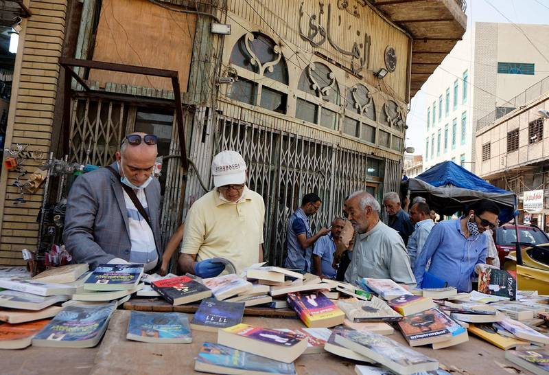 Iraqis check out books sold by a street vendor after measures of social distancing were eased by the authorities, ahead of the fasting month of Ramadan, in central Baghdad on April 22, 2020, during the novel coronavirus pandemic crisis.  / AFP / SABAH ARAR