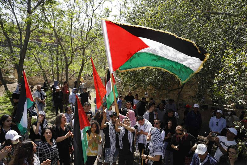Arab Israelis protestors hold up the Palestinian flag in the village of Hittin as they march for the right of return for Palestinian refugees who fled their homes or were expelled during the 1948 war that followed the creation of the state of Israel, near Tiberias in northern Israel, on April 15, 2021. Israelis are marking Independence Day, celebrating the 73th year since the founding of the Jewish State in 1948 according to the Jewish calendar. / AFP / Ahmad GHARABLI
