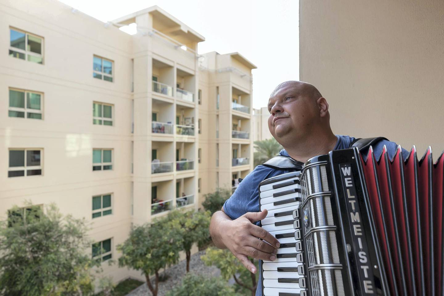Dubai, United Arab Emirates - Reporter: Rory Reynolds: Boki Prekovic, a Serbian accordion player keeping residents stuck at home entertained from his balcony. Thursday, March 19th, 2020. The Greens, Dubai. Chris Whiteoak / The National