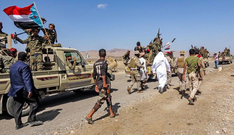 TOPSHOT - Fighters loyal to Yemen's separatist Southern Transitional Council (STC) travel in a convoy in Yemen's southern Abyan province, on December 13, 2020, as part of a withdrawal according to a power sharing agreement brokered in the Saudi capital Riyadh days earlier. Yemen's internationally recognised government and southern separatists are expected to form a cabinet within the week according to Saudi officials, kicking off the implementation of a Riyadh-sponsored power sharing agreement. The agreement struck late last year was designed to mend a rift between the secessionist Southern Transitional Council (STC) and the government, both technically allies in the war against Huthi rebels who have seized much of Yemen's north. / AFP / -
