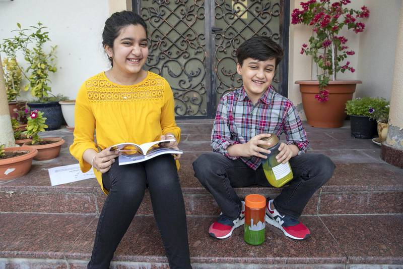 DUBAI UNITED ARAB EMIRATES. 25 NOVEMBER 2020. Safa Kidwai with the book she has published on Amazo and her brother younger Abdullah with his recycled glass jars. (Photo: Antonie Robertson/The National) Journalist: Deepthi Nair Section: National.