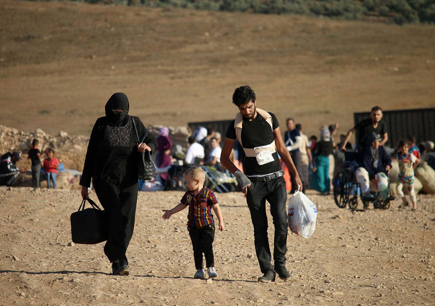 Syrians walk carrying their belongings on August 22, 2017 after crossing the Syria-Jordan border near the town of Nasib as they return to their homes following a US-Russia ceasefire brokered in three southern provinces, Daraa, Quneitra, and Sweida earlier in the year.  / AFP PHOTO / Mohamad ABAZEED