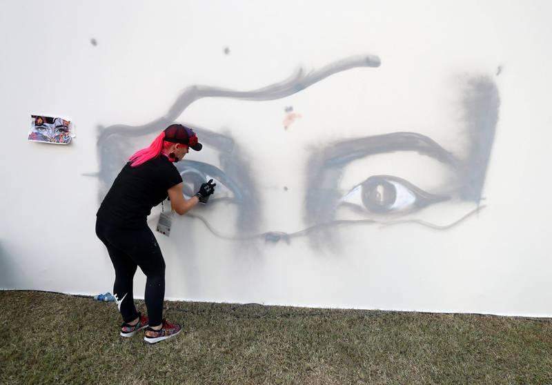 Dubai, United Arab Emirates - October 20, 2019: Graffiti artist Dina Saadi at the One year to go celebrations. Sunday the 20th of October 2019. Burj Park, Dubai. Chris Whiteoak / The National