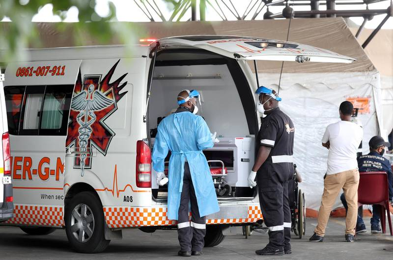 Health workers chat near an ambulance  at the parking lot of the Steve Biko Academic Hospital, amid a nationwide coronavirus disease (COVID-19) lockdown, in Pretoria, South Africa, January 11, 2021. REUTERS/Siphiwe Sibeko