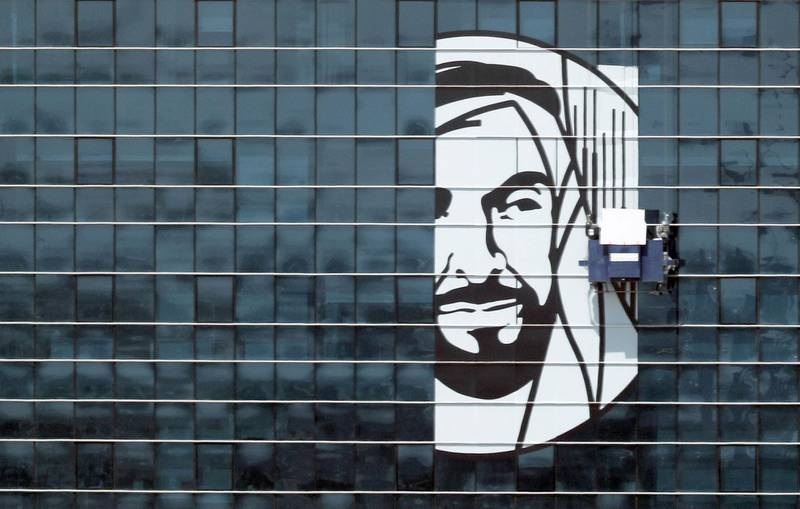 Abu Dhabi - 25th Mar 2018 - Workers sticking a poster of Father of Nation Late Sheikh Zayed bin Sultan Al Nahyan poster on the FAB headquarter building near Khalifa park to mark the Year of Zayed around UAE. Ravindranath K / The National