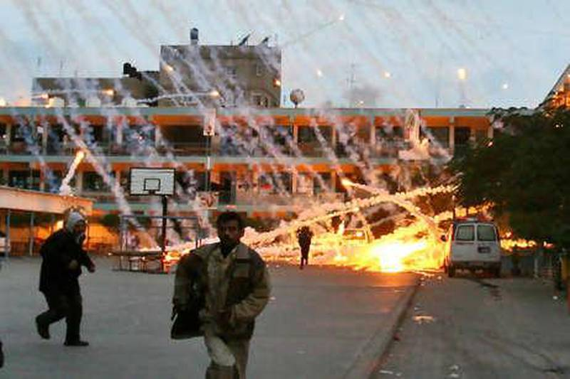 (FILES) -- A picture dated January 17, 2009 shows Palestinian civilians and medics runing to safety during an Israeli strike over a UN school in Beit Lahia, northern Gaza Strip. Israel will restrict its use of white phosphorus munitions and seek to limit civilian casualties in future wars, it said in a report to the UN secretary general released in July 2010. AFP PHOTO / MOHAMMED ABED