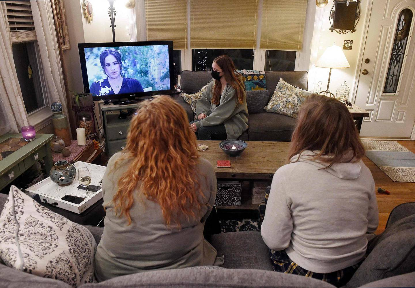 This photo illustration shows people wearing face masks, watch a televised conversation between Meghan, Duchess of Sussex and US host Oprah Winfrey, in Arlington, Virginia March 7, 2021. Britain's royal family on Sunday braced for further revelations from Prince Harry and his American wife, Meghan, as a week of transatlantic claim and counter-claim reaches a climax with the broadcast of their interview with Oprah Winfrey. The two-hour interview with the US TV queen is the biggest royal tell-all since Harry's mother princess Diana detailed her crumbling marriage to his father Prince Charles in 1995.  / AFP / OLIVIER DOULIERY