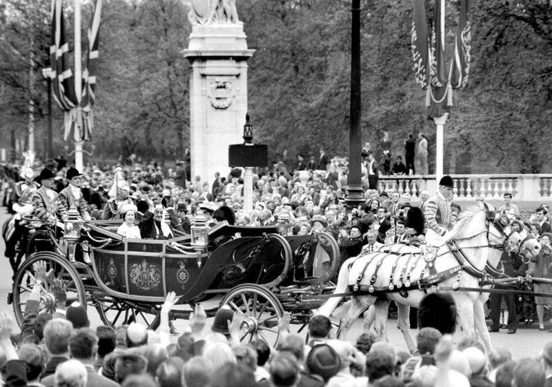 King Faisal of Saudi Arabia waves in response to the crowd lining the Mall as he drives with the Queen to Buckingham Palace on arrival for his eight-day state visit.