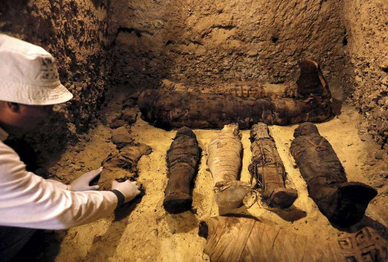 A Egyptian archaeologist examines mummies inside a tomb during the presentation of a new discovery at Tuna el-Gebel archaeological site in Minya Governorate, Egypt, February 2, 2019. REUTERS/Amr Abdallah Dalsh