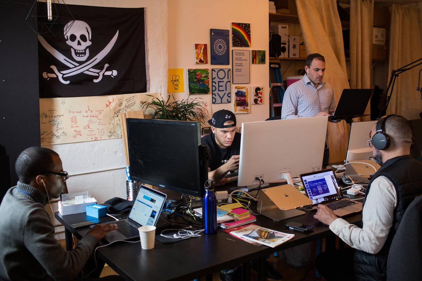 Employees work on computers at the ConsenSys Inc. office in the Brooklyn borough of New York, U.S., on Thursday, March 29, 2018. The employees ofConsenSys, the blockchain startup co-created by Ethereum guruJoseph Lubin, have taken over the space at 49 Bogart Street in the Bushwick neighborhood of Brooklyn. Photographer: Holly Pickett/Bloomberg