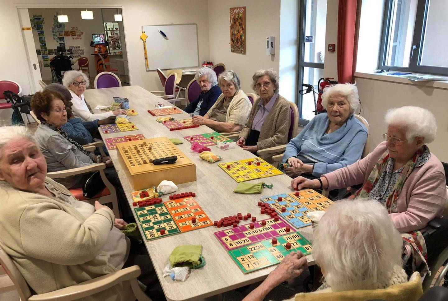 In this photo provided by the Vilanova nursing home, residents play inside the Vilanova nursing home on April 30 2020 in Corbas, central France. As the coronavirus cut a deadly path through nursing homes, staff locked themselves in with the 106 residents at this care home to stop COVID-19 coronavirus from infecting and killing the vulnerable older adults in their care, and they have not had any people falling victim to the virus.(Valerie Martin via AP)