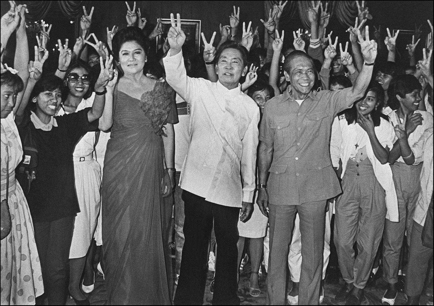 """Surrounded by supporters, Philippines President Ferdinand Marcos (C), his wife Imelda and his Vice President Arturo Tolentino make the """"V"""" sign for victory of the presidential elections, 16 February 1986 in Manila at the Malacanang Palace. (Photo by HO / AFP)"""