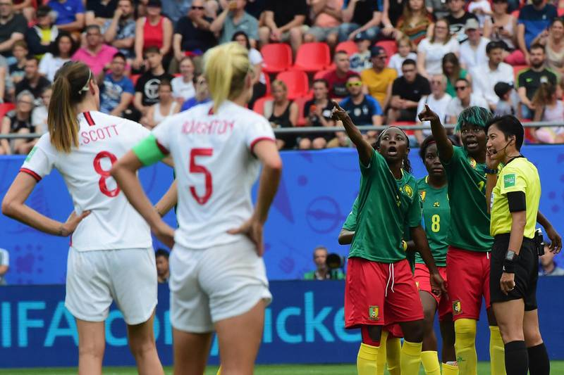 VALENCIENNES, FRANCE - JUNE 23:  Players of Cameroon speak with referee Qin Liang during the 2019 FIFA Women's World Cup France Round Of 16 match between England and Cameroon at Stade du Hainaut on June 23, 2019 in Valenciennes, France.  (Photo by Pier Marco Tacca/Getty Images)