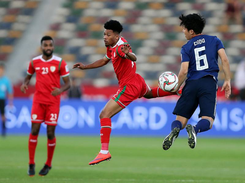 Abu Dhabi, United Arab Emirates - January 13, 2019: Endo Wataru of Japan and Jameel Al Yahmadi of Oman battle during the game between Japan and Oman in the Asian Cup 2019. Sunday, January 13th, 2019 at Zayed Sports City Stadium, Abu Dhabi. Chris Whiteoak/The National