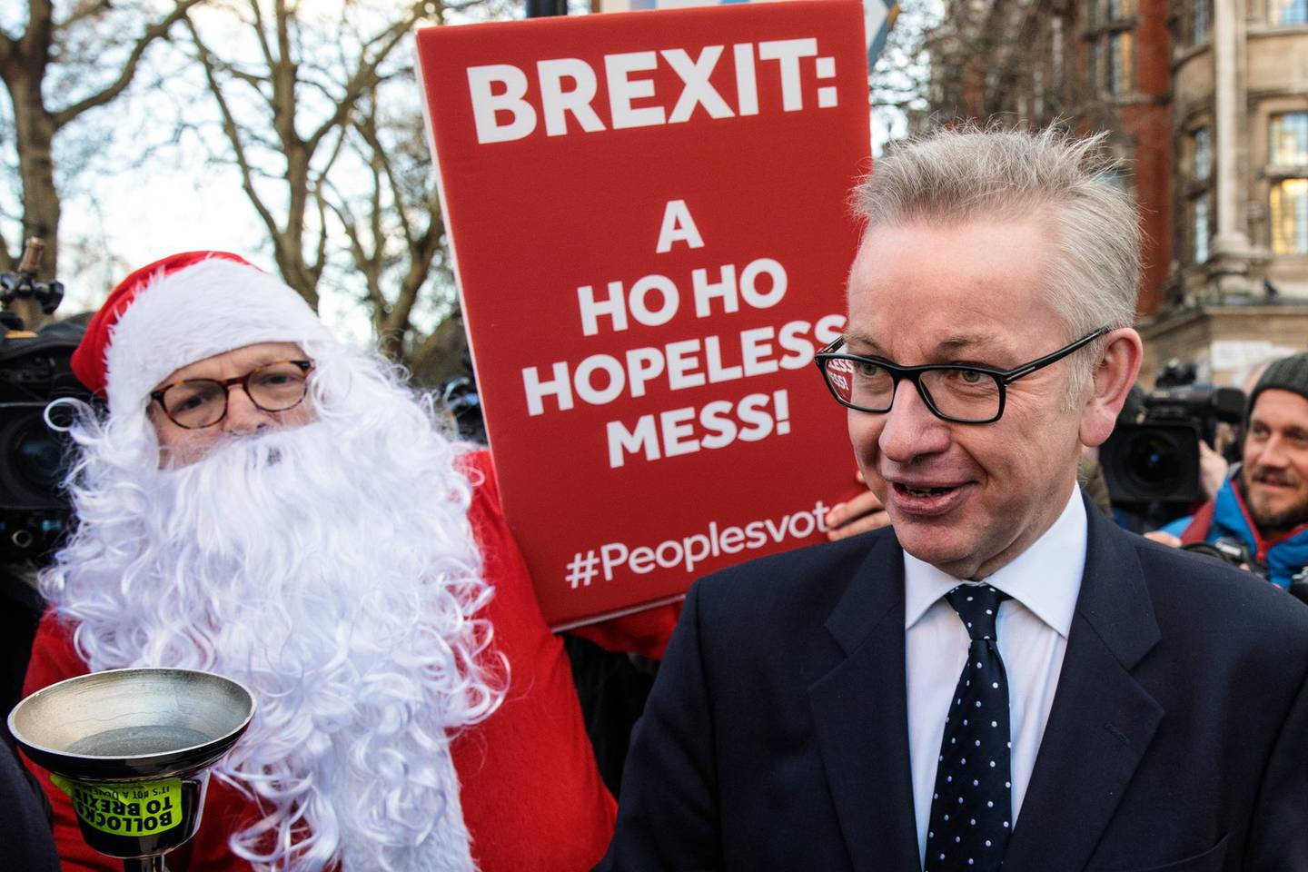 LONDON, ENGLAND - DECEMBER 12: Environment Secretary Michael Gove is accosted by a protester in a Father Christmas outfit after speaking the media in Westminster on December 12, 2018 in London, England. Sir Graham Brady, the chairman of the 1922 Committee, has received the necessary 48 letters (15% of the parliamentary party) from Conservative MP's that will trigger a vote of no confidence in Prime Minister Theresa May. (Photo by Jack Taylor/Getty Images)