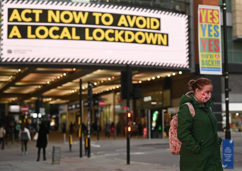 """People wearing face masks walk through the shopping area in the city centre of Manchester, north west England on October 8, 2020.  Pubs and restaurants in coronavirus hotspots look set to face fresh restrictions after Downing Street said new data suggests there is """"significant"""" transmission taking place in hospitality settings. A """"range of measures"""" is being looked at, with a particular focus on northern England, where it says infection rates are rising fastest. / AFP / Oli SCARFF"""