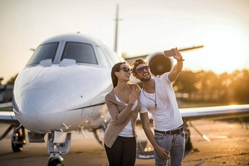 Young urban heterosexual couple with sunglasses standing at the airport track in front of private jet airplane and posing for a selfie. Man is holding the camera and taking a picture. Bright sunlight is in the background.