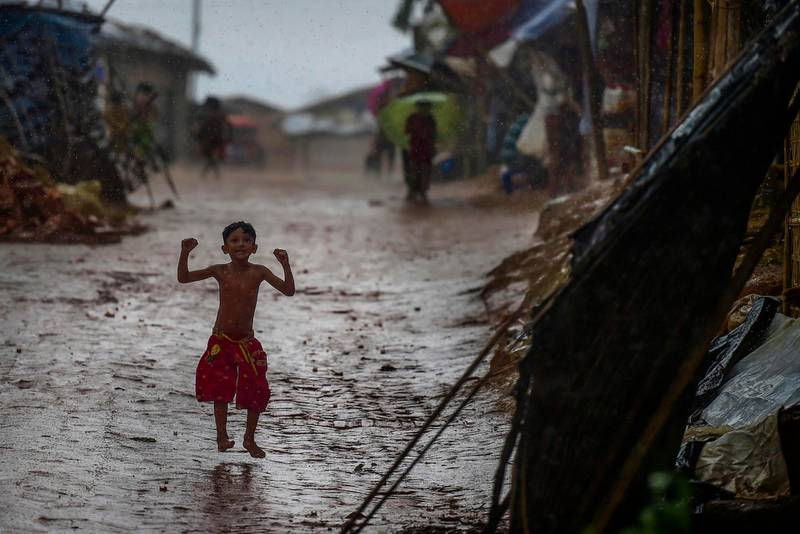 A Rohingya refugee child plays during a monsoon rainfall at Kutupalong refugee camp in Ukhia on July 23, 2019. / AFP / MUNIR UZ ZAMAN
