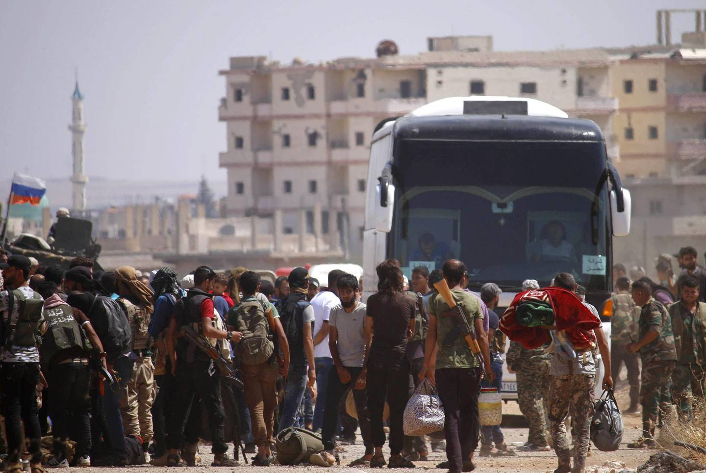"""Syrian rebels and their families stand by buses to be evacuated from Daraa city, on July 15, 2018, as Syrian government forces heavily bombed the neighbouring province of Quneitra making a ground advance in the zone.        Syrian rebels and their relatives began evacuating the southern city of Daraa today under a deal to bring the """"cradle"""" of the country's uprising back into the government's fold. / AFP / Mohamad ABAZEED"""