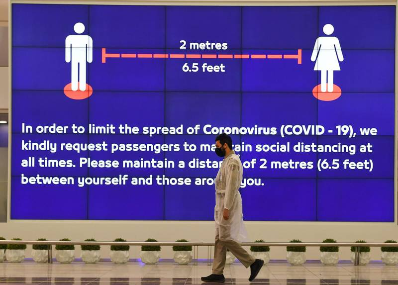 An Employee at Dubai International Airport, walk past a poster reminding passengers to keep a safe distance from each other, after the resumption of scheduled operations by the Emirati carrier, amid the ongoing novel coronavirus pandemic crisis, on May 22, 2020.       / AFP / Karim SAHIB