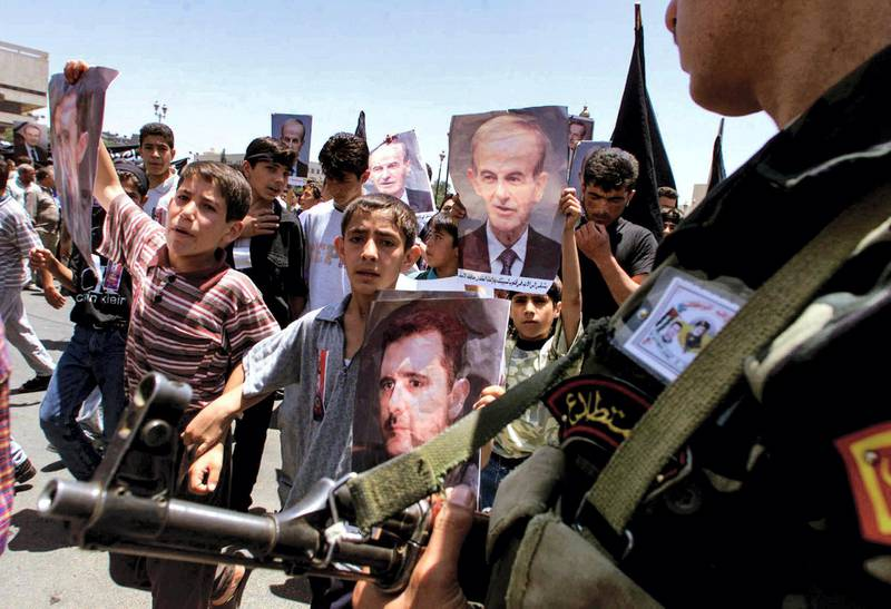 (FILES) In this file photo taken on June 12, 2000, a presidential guard watches Syrian youths as they march through the streets of the capital Damascus with portraits of late president Hafez al-Assad and his son Bashar. - President Bashar al-Assad, whose family has ruled Syria for over half a century, faces an election this week meant to cement his image as the only hope for recovery in the war-battered country, analysts say. (Photo by Patrick BAZ / AFP)