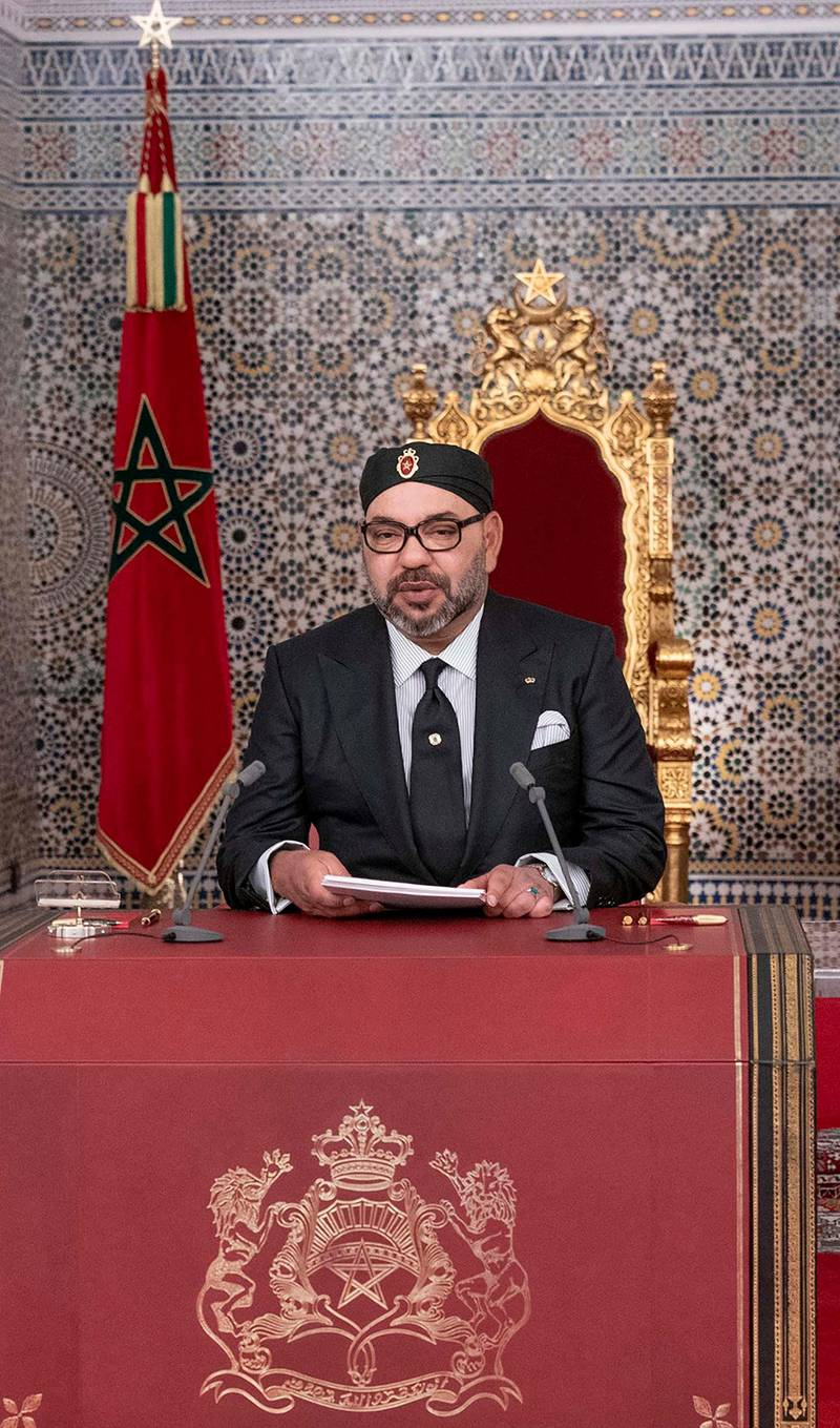 """This handout picture provided by the Moroccan Royal Palace on July 29, 2019 shows Morocco's King Mohammed VI (C) delivering a speech marking the 20th anniversary of his accession to the throne, with his brother Prince Moulay Rachid (R) and son Prince Moulay Hassan (L) seated alongside him, in the northern city of Tetouan overlooking the Mediterranean. (Photo by - / MAP / AFP) / == RESTRICTED TO EDITORIAL USE - MANDATORY CREDIT """"AFP PHOTO /HO/ MOROCCAN ROYAL PALACE"""" - NO MARKETING NO ADVERTISING CAMPAIGNS - DISTRIBUTED AS A SERVICE TO CLIENTS =="""