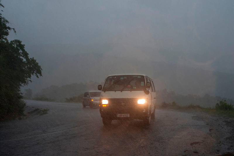 This picture taken on March 15, 2019 shows vehicules as rain, which is believed to be the beginning of Tropical cyclone Idai coming from central Mozambique, falls in the flooded districts of Chikwawaa and Nsanje in southern Malawi. At least 56 people have died in flood-hit areas as of March 13, according to the government, while 577 had been injured and almost 83,000 people have been displaced. / AFP / AMOS GUMULIRA