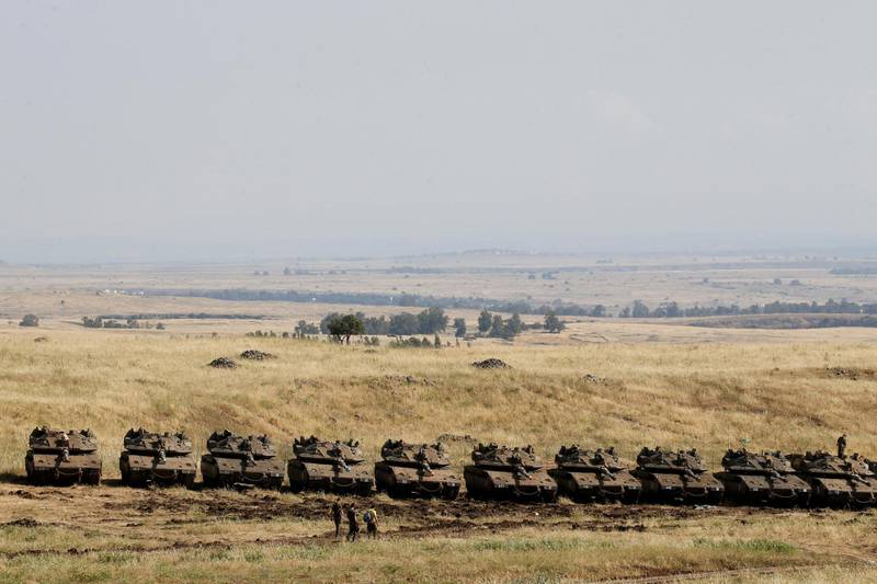 Israeli soldiers walk past tanks near the border with Syria in the Israeli-occupied Golan Heights, Israel May 11, 2018. REUTERS/Baz Ratner