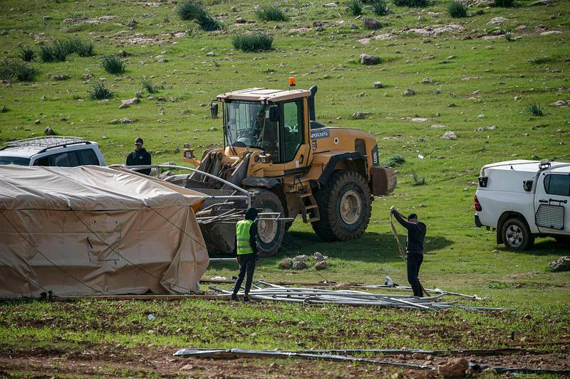 Israeli workers dismantle tents during a demolition operation of a Palestinian bedouin encampment in the area of Humsa, east of the village of Tubas in the north of the occupied West Bank on February 22, 2021.  / AFP / JAAFAR ASHTIYEH