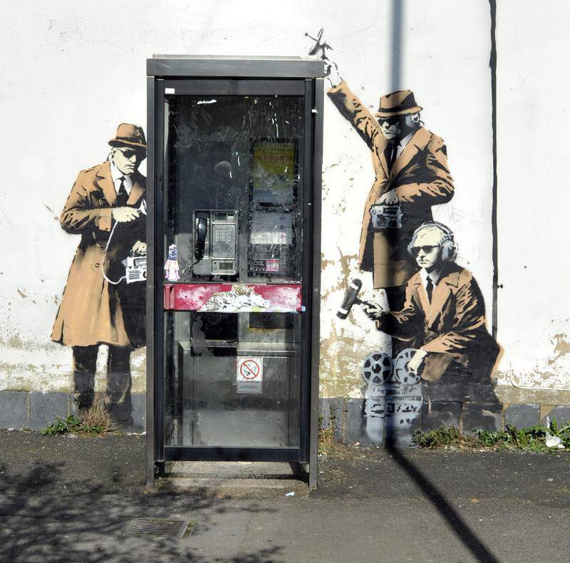 epaselect epa04167836 A general view of a payphone where a new mural believed to be by graffiti artist 'Banksy' was discovered in a residential street in Cheltenham, Britain, 15 April 2014. The painting showing intelligence agents engaged in wiretapping appeared next to a phone booth over the weekend and has yet to be authenticated. The new artwork comes in the wake of the storm over surveillance by British intelligence agency GCHQ and US intelligence agency NSA revealed by US whistleblower Edward Snowden. GCHQ is also based in Cheltenham.  EPA/NEIL MUNNS