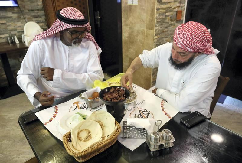 Abu Dhabi, United Arab Emirates - July 24, 2019: Two gentlemen enjoy their dinner. Al Mufraka restaurant, one of Abu DhabiÕs small number of Sudanese restaurants. Wednesday the 24th of July 2019. Abu Dhabi. Chris Whiteoak / The National