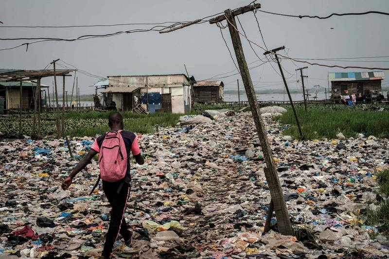 - AFP PICTURES OF THE YEAR 2019 -   A man walks on plastic waste, used to reclaim a swamp so that the land can be developed for housing, in the Mosafejo area of Lagos on February 12, 2019. Nigeria, which elects a new president on February 16, is Africa's most populous nation and leading oil producer but is dogged by poverty and insecurity. -   / AFP / Yasuyoshi CHIBA