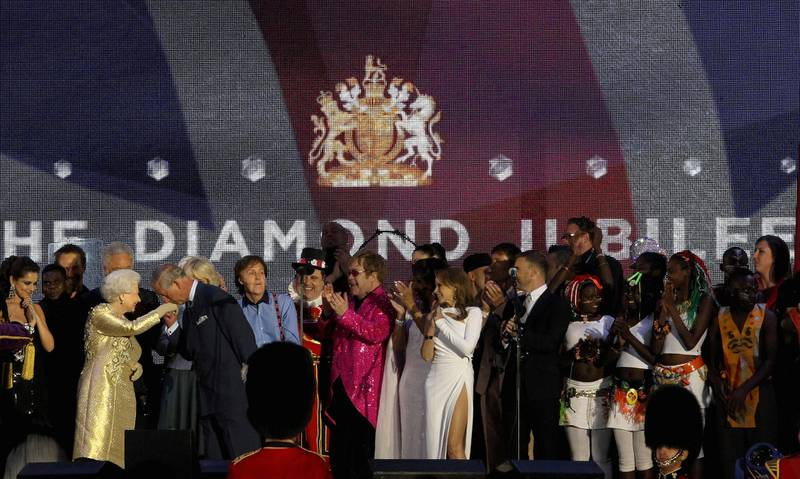LONDON, ENGLAND - JUNE 04:  HM Queen Elizabeth II and The Prince of Wales (L) on stage with artists during the Diamond Jubilee concert at Buckingham Palace on June 4, 2012 in London, England. For only the second time in its history the UK celebrates the Diamond Jubilee of a monarch. Her Majesty Queen Elizabeth II celebrates the 60th anniversary of her ascension to the throne. Thousands of well-wishers from around the world have flocked to London to witness the spectacle of the weekend's celebrations.  (Photo by Dan Kitwood/Getty Images)