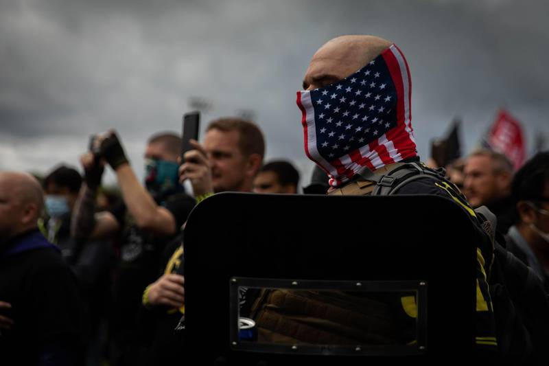 """A man hold his hand to his heart as a Proud Boys organizer recites the Pledge of Allegiance during a Proud Boys rally at Delta Park in Portland, Oregon on September 26, 2020. Far-right group """"Proud Boys"""" members gather in Portland to show support to US president Donald Trump and to condemn violence that have been occurring for more than three months during """"Black Lives Matter"""" and """"Antifa"""" protests.   / AFP / Maranie R. STAAB"""