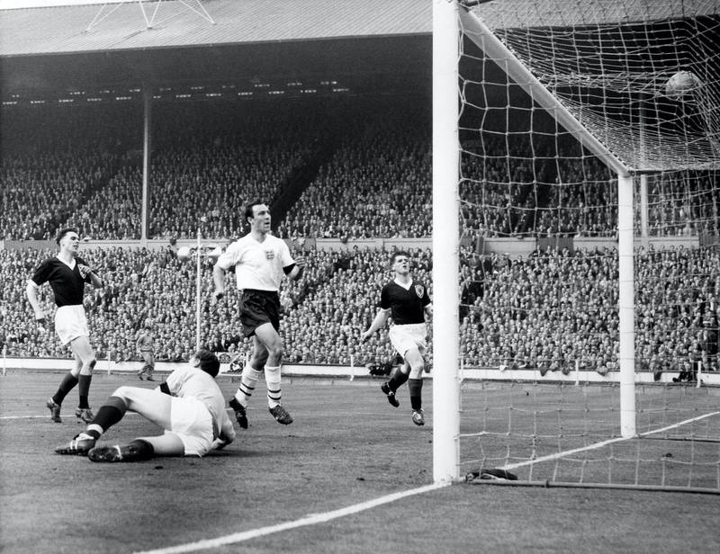 England's Jimmy Greaves (second r) scores his team's third goal past Scotland goalkeeper Frank Haffey (second l), watched by Scotland's Bobby Shearer (r) and Robert McCann (l)  (Photo by S&G/PA Images via Getty Images)
