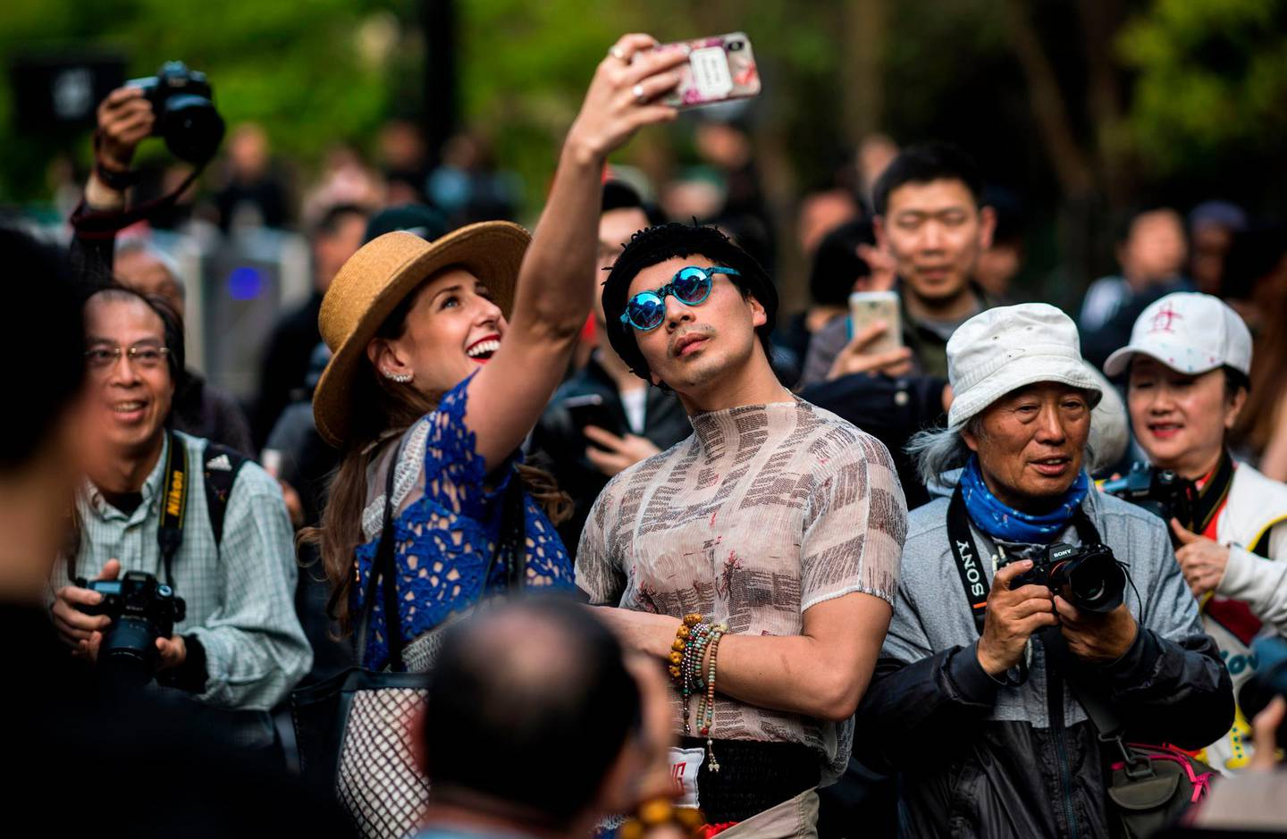 A couple poses for a selfie as they arrive at the Shanghai Fashion Week in Shanghai on March 31, 2018. / AFP PHOTO / Johannes EISELE
