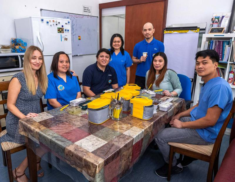 Abu Dhabi, U.A.E., August 28,, 2018.  British Veterinary Centre's Filipino staff were ordering their lunch each day from the same restaurant, the Khalidyah branch of Royal Pinoy but they got fed up of all the plastic waste.  So the admin manager, Jennifer Hale, ordered reusable lunch kits which the restaurant now refills each day for them. --- (L) Jennifer Hale with her Filipino Staff during lunch break.Victor Besa/The NationalSection:  NA