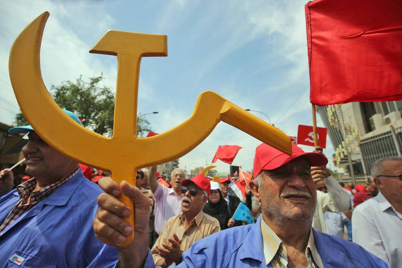A supporter of the Iraqi Communist Party holds the communist symbol of the hammer and sickle during a march celebrating the International Workers Day in the Iraqi capital  Baghdad on May 1, 2018.  / AFP PHOTO / AHMAD AL-RUBAYE