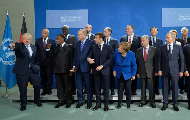 BERLIN, GERMANY - JANUARY 19: British Prime Minister Boris Johnson (L) gestures as other participants, including German Chancellor Angela Merkel, French President Emmanuel Macron, Russian President Vladimir Putin, U.S. Secretary of State Mike Pompeo and Turkish President Recep Tayyip Erdogan, look before a group photo at an international summit on securing peace in Libya at the Chancellery on January 19, 2020 in Berlin, Germany. Leaders of nations and organizations linked to the current conflict are meeting to discuss measures towards reaching a consensus between the warring sides and ending hostilities.   (Photo by Sean Gallup/Getty Images)