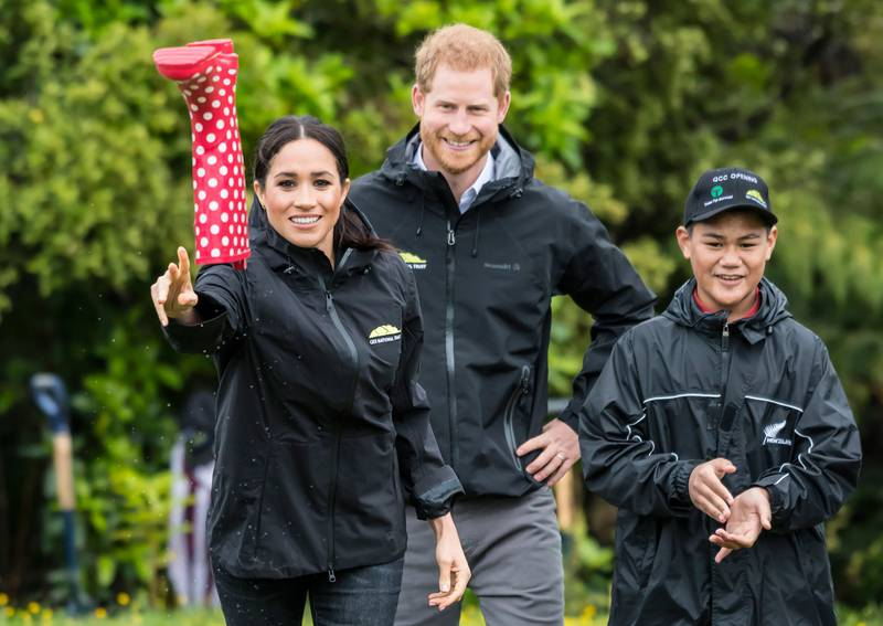 """Britain's Meghan, Duchess of Sussex participates in a gumboot throwing competition with Prince Harry after unveiling a plaque dedicating 20 hectares of native bush to the Queen's Commonwealth Canopy project at The North Shore Riding Club in Auckland on October 30, 2018. Meghan Markle displayed an unexpected talent for """"welly wanging"""" in Auckland on October 30, gaining bragging rights over husband Prince Harry after they competed in the oddball New Zealand sport. / AFP / POOL / STR"""