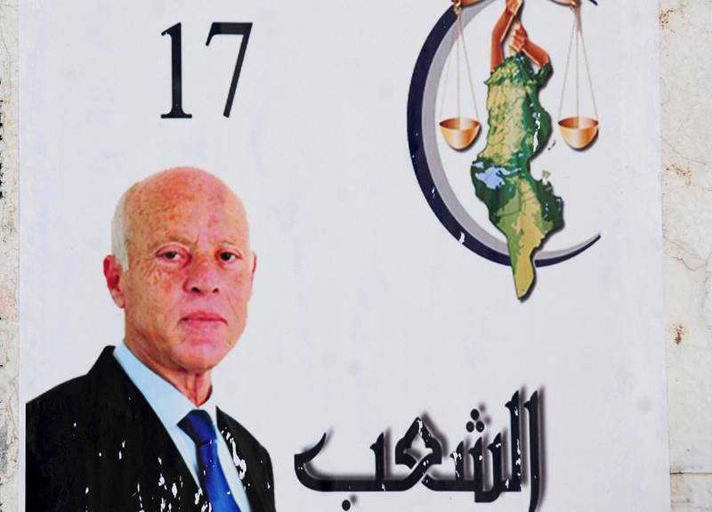 An electoral poster for independent presidential candidate Kais Saied, a constitutional law professor without a party, is pictured Monday, Sept. 16, 2019 in Tunis. A jailed media magnate and an independent outsider appeared likely to face off in Tunisia's presidential runoff, after a roller coaster first-round race in the country that unleashed the Arab Spring pro-democracy uprisings. (AP Photo/Hassene Dridi)