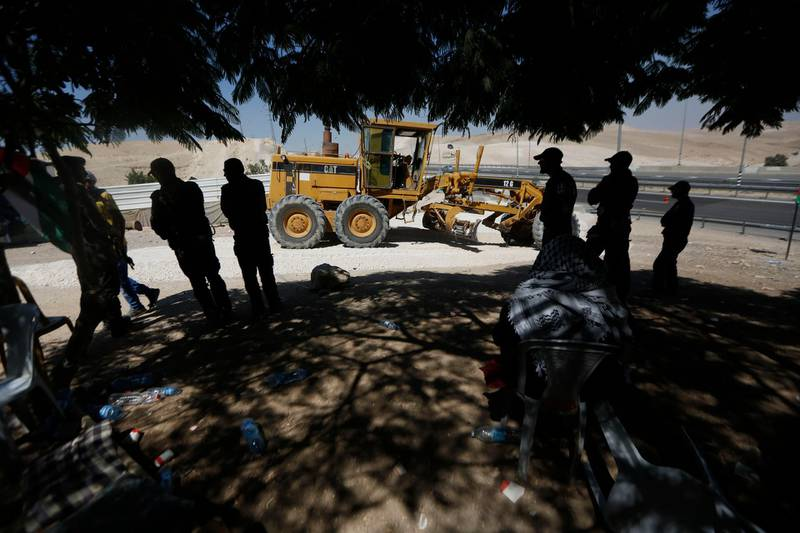 Palestinians watch as an Israeli bulldozer works in the West Bank hamlet of Khan al-Ahmar, Thursday, July 5, 2018. The Bedouin village outside the Kfar Adumim settlement, is set to be demolished on an unknown date after Israel's Supreme Court approved the move in May. (AP Photo/Majdi Mohammed)